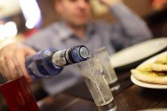 El hombre llena un vidrio de vodka Fotos de archivo libres de regalías