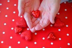 El hombre lleva a cabo el corazón del brillo de la tarjeta del día de San Valentín Imagen de archivo