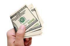 El hombre lleva a cabo en su mano cientos dólares y paga Foto de archivo libre de regalías