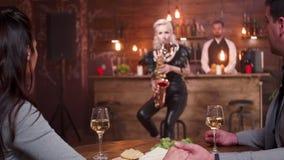 El hombre lleva a cabo la mano de su prometido mientras que un saxofonista femenino juega apasionado metrajes