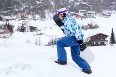 El hombre lleva el snowboard en la montaña Fotos de archivo libres de regalías