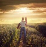 El hombre lleva a la mujer en el campo del verano en puesta del sol Fotos de archivo libres de regalías