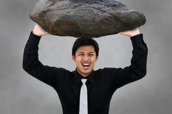 El hombre lleva la roca y subraya la acción Fotos de archivo libres de regalías