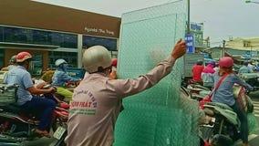 El hombre lleva pedazos de cristal grandes en la vespa en calle del tráfico almacen de video