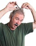 El hombre loco corta su pelo Imagen de archivo libre de regalías