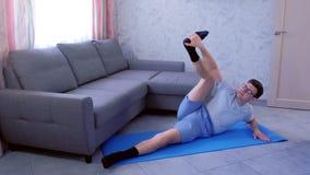 El hombre loco del empollón está intentando estirar sus piernas que ponen en la estera en casa Concepto del humor del deporte almacen de video