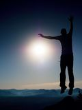El hombre loco está saltando en la montaña Silueta del hombre de salto y del cielo hermoso de la puesta del sol Fotos de archivo