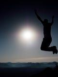 El hombre loco joven está saltando en roca Silueta del hombre de salto Foto de archivo