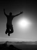 El hombre loco joven está saltando en roca Silueta del hombre de salto Fotos de archivo