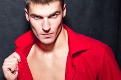 El hombre macho moderno joven en camisa roja está presentando Fotografía de archivo