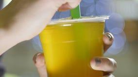 El hombre macro pone la paja plástica verde en la taza con la bebida amarilla almacen de metraje de vídeo