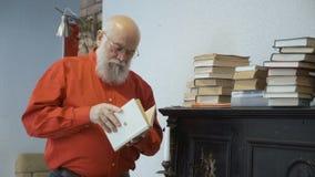 El hombre maduro busca la información en libro viejo almacen de metraje de vídeo