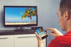 El hombre maduro con Smartphone conectó con una película de observación de la TV en casa fotografía de archivo libre de regalías