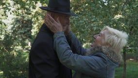 El hombre maduro puso el sombrero y la señora endereza sombrero en el parque almacen de metraje de vídeo