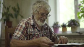 El hombre maduro que mira sus fotos viejas y recuerda su juventud almacen de video