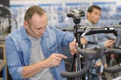 El hombre maduro que repara la bici rueda adentro propia tienda Imágenes de archivo libres de regalías