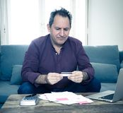 El hombre maduro trastornado subrayó sobre deudas de la tarjeta de crédito y finanzas que consideraban no felices de los pagos fotos de archivo libres de regalías