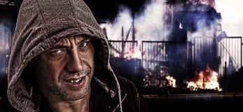 El hombre malvado asustadizo con la capilla en un fondo de la calle se amotina. Imágenes de archivo libres de regalías