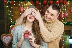 El hombre mantiene sus ojos de la novia cubiertos mientras que ella que da el regalo, sorpresa romántica para el día de tarjetas  Fotografía de archivo libre de regalías