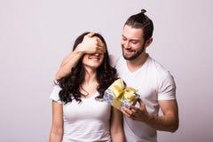 El hombre mantiene sus ojos de la novia cubiertos mientras que ella que da un regalo Foto de archivo