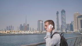 El hombre marca el número en el teléfono y habla en el fondo del panorama de Dubai Primer de la mano almacen de metraje de vídeo