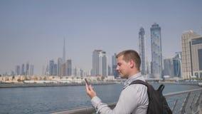 El hombre marca el número en el teléfono y habla en el fondo del panorama de Dubai Primer de la mano metrajes