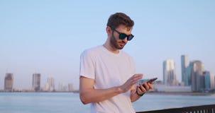 El hombre marca el n?mero en el tel?fono y habla en el fondo del panorama de Dubai Primer de la mano almacen de video