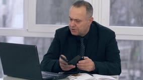 El hombre mayor agitated con la tarjeta de crédito utiliza el ordenador portátil y la calculadora en oficina moderna almacen de video