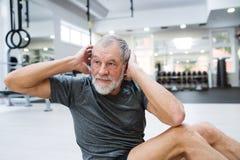 El hombre mayor apto en el gimnasio que trabaja su ABS, haciendo cruje Imagenes de archivo