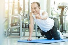 El hombre mayor asiático empuja hacia arriba en el gimnasio Imagen de archivo