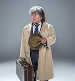 El hombre mayor como detective o jefe de la mafia en fondo gris del estudio Imágenes de archivo libres de regalías