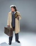 El hombre mayor como detective o jefe de la mafia en fondo gris del estudio Fotografía de archivo libre de regalías