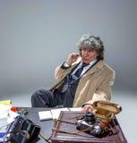 El hombre mayor como detective o jefe de la mafia en fondo gris del estudio Fotos de archivo libres de regalías