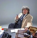 El hombre mayor como detective o jefe de la mafia en fondo gris del estudio Imagenes de archivo