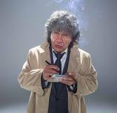 El hombre mayor como detective o jefe de la mafia en fondo gris del estudio Fotografía de archivo