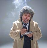 El hombre mayor como detective o jefe de la mafia en fondo gris del estudio Foto de archivo libre de regalías