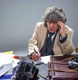 El hombre mayor como detective o jefe de la mafia en fondo gris del estudio Foto de archivo