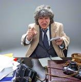 El hombre mayor como detective o jefe de la mafia en fondo gris del estudio Imagen de archivo libre de regalías