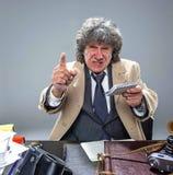 El hombre mayor como detective o jefe de la mafia en fondo gris del estudio Imagen de archivo