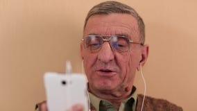 El hombre mayor comunica con un smartphone Hombre con el teléfono móvil metrajes