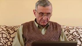 El hombre mayor comunica a través de un ordenador portátil Hombre con el cuaderno metrajes