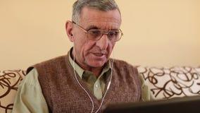 El hombre mayor comunica vía el ordenador portátil Hombre con el cuaderno almacen de video