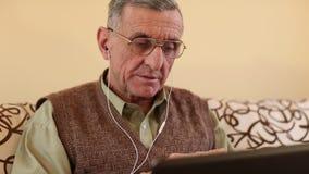 El hombre mayor comunica vía el ordenador portátil Hombre con el cuaderno metrajes