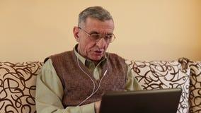 El hombre mayor comunica vía el ordenador portátil Hombre con el cuaderno almacen de metraje de vídeo