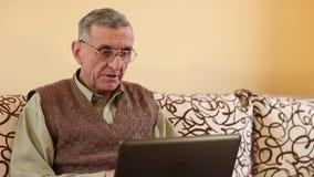 El hombre mayor comunica vía el ordenador portátil Hombre en un sofá con un cuaderno almacen de video