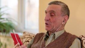 El hombre mayor comunica vía smartphone Hombre con el teléfono celular almacen de video