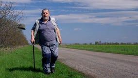 El hombre mayor con el bastón camina en un borde de la carretera en el día de primavera ventoso almacen de metraje de vídeo