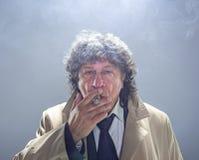 El hombre mayor con el cigarro como detective o jefe de la mafia en fondo gris del estudio Imagen de archivo