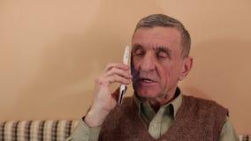 El hombre mayor con el smartphone blanco habla, sonríe y gesticula almacen de metraje de vídeo
