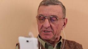 El hombre mayor con el smartphone blanco habla y gesticula almacen de metraje de vídeo